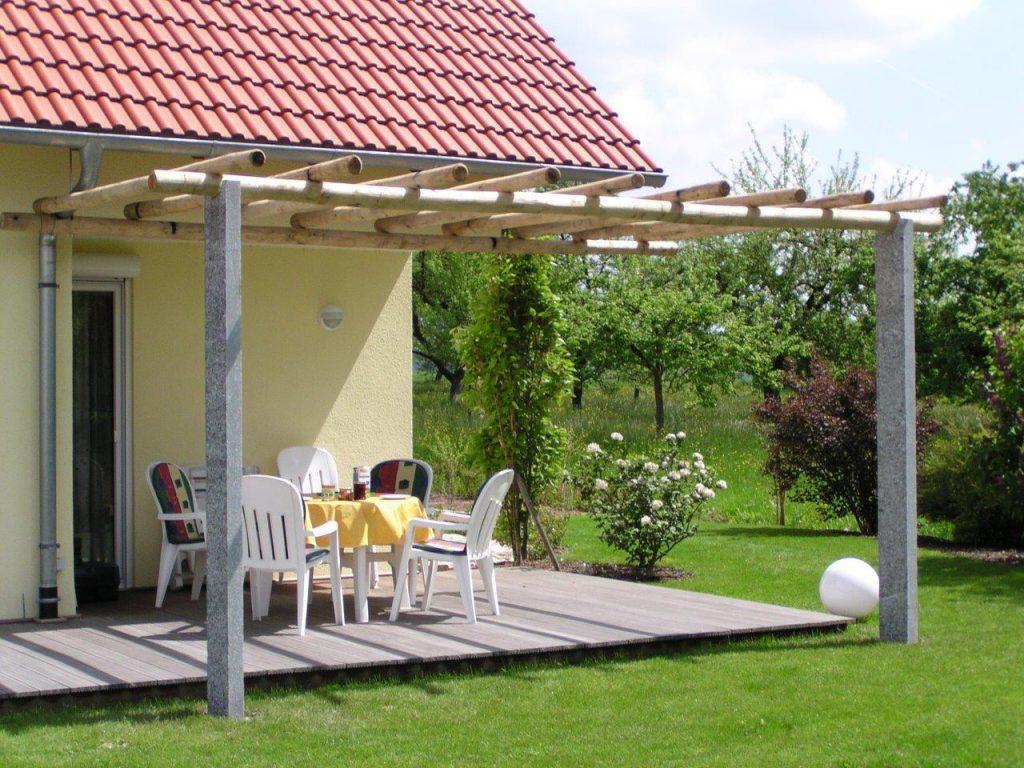 Pergola aus Naturstein mit Kastanien Rundholz überdeckt für Ihren Garten. Fragen Sie nach einer Offerte an.